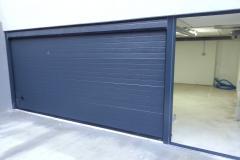 Puerta seccional  acanalada con dintel superior gris RAL 7016 y fijo lateral con cristal